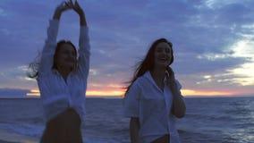 Meisjes bij het overzees in de avond stock footage