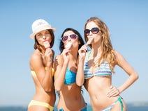 Meisjes in bikinis met roomijs op het strand Royalty-vrije Stock Foto's
