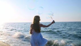 Meisjes blazende bellen op strand in langzame motie Een jong meisje blaast zeepbels in de avond, tijdens zonsondergang Looppas  stock footage