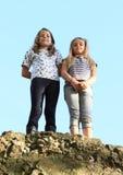 Meisjes bovenop rots Stock Foto's