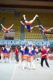 Meisjes - de deelnemers van de Leider van het cheerleadersteam presteren Stock Foto's