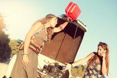 Meisjes dichtbij een auto zonder brandstof royalty-vrije stock foto