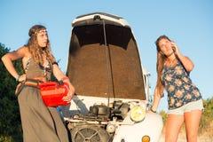 Meisjes dichtbij een auto zonder brandstof royalty-vrije stock afbeeldingen