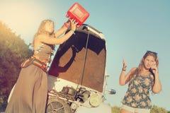 Meisjes dichtbij een auto zonder brandstof stock afbeeldingen