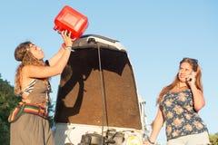 Meisjes dichtbij een auto zonder brandstof stock foto's