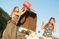 Meisjes dichtbij een auto zonder brandstof royalty-vrije stock afbeelding