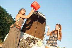 Meisjes dichtbij een auto zonder brandstof stock afbeelding