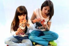 Meisjes die aardbeien en slagroom eten Stock Fotografie