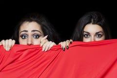 Meisjes die achter rode doek verbergen stock afbeelding