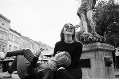 Meisjes die bij de fontein zitten De vakantieconcept van de zomer stock afbeelding