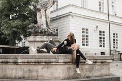 Meisjes die bij de fontein zitten De vakantieconcept van de zomer royalty-vrije stock foto's