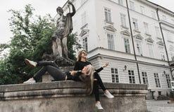 Meisjes die bij de fontein zitten De vakantieconcept van de zomer stock afbeeldingen