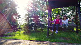 Meisjes die bij in openlucht werf slingeren stock footage