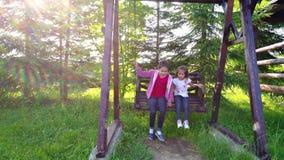 Meisjes die bij in openlucht werf slingeren stock videobeelden