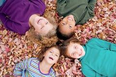 Meisjes die in Bladeren spelen Stock Foto's