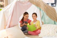 Meisjes die boek in jonge geitjestent thuis lezen stock fotografie