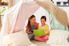 Meisjes die boek in jonge geitjestent thuis lezen royalty-vrije stock afbeelding
