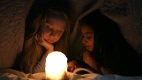 Meisjes die boek lezen onder deken bij nacht stock video