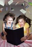 Meisjes die boek op bed lezen Stock Afbeeldingen