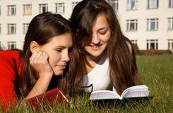 Meisjes die de boeken op het gazon lezen stock foto's