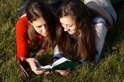 Meisjes die de boeken op het gazon lezen stock afbeeldingen