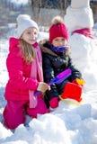 Meisjes die in de winter met schoppen spelen Stock Afbeeldingen