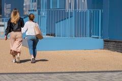 Meisjes die door de universiteit van DE monfort op zonnige dag lopen Stock Foto