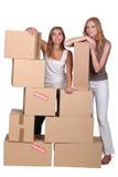 Meisjes die door dozen worden omringd Stock Afbeeldingen