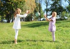 Meisjes die een bal werpen Stock Foto's
