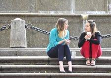 2 meisjes die een ernstig gesprek op de stappen hebben Stock Foto