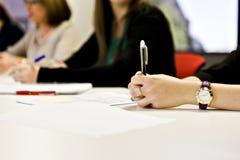 Meisjes die een pen houden die haar hand met een horloge gebruiken royalty-vrije stock afbeeldingen