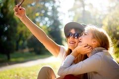 Meisjes die een selfie in het park nemen Stock Afbeelding