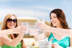 Meisjes die een toost in koffie op het strand maken Stock Afbeeldingen
