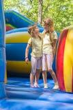 Meisjes die gelukkig bekijkend elkaar door op een opblaasbare trampoline te springen grimassen trekken Stock Foto's