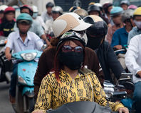 Meisjes die gezichtsmasker in verontreinigde Saigon dragen Stock Foto's