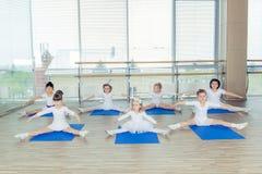 Meisjes die gymnastiek- oefeningen doen of in geschiktheidsklasse uitoefenen stock foto's
