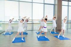 Meisjes die gymnastiek- oefeningen doen of in geschiktheidsklasse uitoefenen royalty-vrije stock fotografie