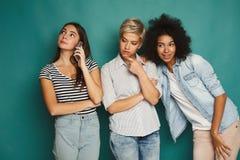 Meisjes die haar bespreking van de vrienden mobiele telefoon afluisteren Stock Foto's