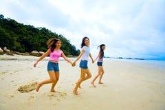 Meisjes die handen houden bij het strand Stock Foto