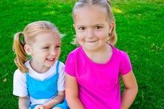 Meisjes die in het gras zitten stock fotografie