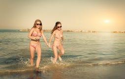Meisjes die in het overzees lopen royalty-vrije stock afbeeldingen
