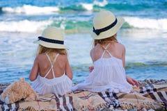 Meisjes die in hoeden op strand zitten Stock Afbeeldingen