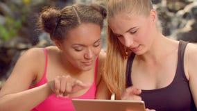 Meisjes die Internet op tablet zoeken openlucht Sluit omhoog van vrienden die Internet surfen stock videobeelden
