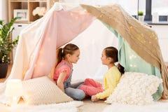 Meisjes die in jonge geitjestent thuis spreken stock afbeeldingen