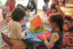 Meisjes die in kleuterschool spelen stock foto's