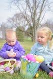 Meisjes die met de Pasen-buiten manden zitten stock fotografie