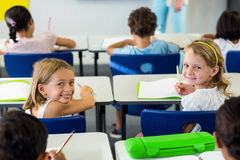 Meisjes die met klasgenoten in klaslokaal zitten stock fotografie