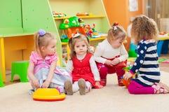 Meisjes die met speelgoed in speelkamer spelen Stock Foto's