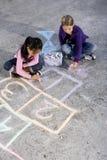 Meisjes die met stoepkrijt spelen royalty-vrije stock afbeelding