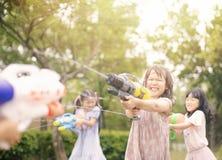 Meisjes die met waterkanonnen spelen op de zomer royalty-vrije stock afbeeldingen